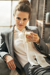 Portrait of business woman with coffee latte in loft apartment