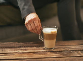 Closeup on business woman taking coffee latte from coffee table