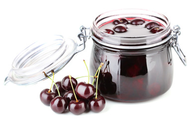Tasty cherry jam in glass jar on wooden table