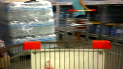 Customer shopping at supermarket with trolley. Video