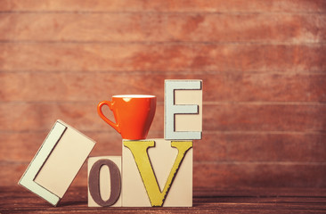 Tea or coffee cup with word Love on wooden table.
