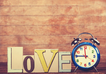 Alarm clock and word Love on wooden table.