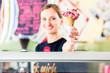 Leinwandbild Motiv Eisverkäuferin portioniert Kugel Eiscreme in Waffel