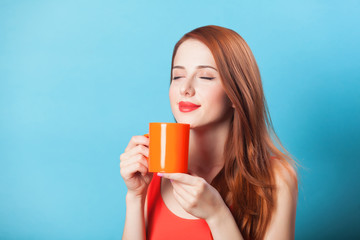 Redhead women with cup on blue background.