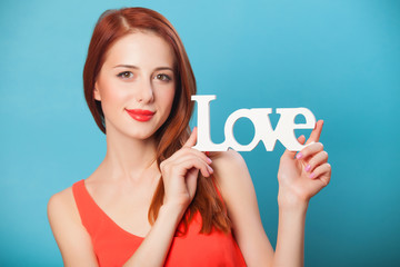 Happy redhead women with word Love on blue background.