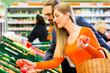 Paar wählt Gemüse im Lebensmittelmarkt aus