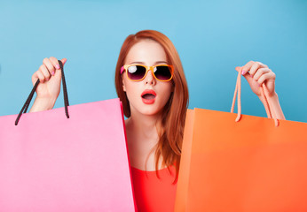 Surprised redhead women holding shopping bags on blue background