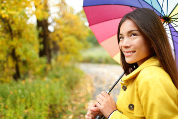 Woman happy with umbrella under the rain