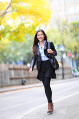 Young urban professional woman in walking in city