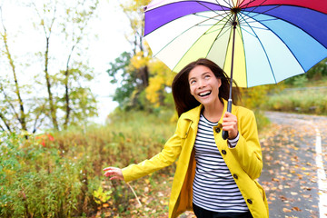 Autumn woman happy in rain running with umbrella