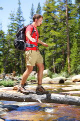 Hiking man hiker crossing river in Yosemite