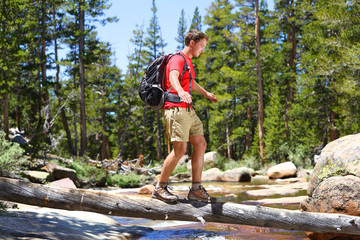 Hiker man hiking crossing river in Yosemite