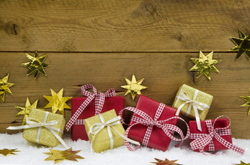 Goldene und rote Weihnachtsgeschenke auf Holz Hintergrund