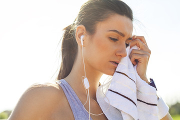 Young woman resting and wiping with towel after running.
