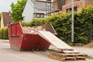 Ein gefüllter roter Bauschuttcontainer vor einer Hausbaustelle