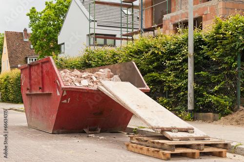 Leinwandbild Motiv Ein gefüllter roter Bauschuttcontainer vor einer Hausbaustelle