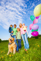Parents, kids and dog stand with balloons in park