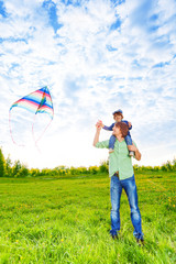Smiling father holds kid and watches kite in air