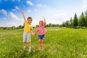 Boy and girl hold hands with second hand up