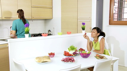 Two women preparing salad with tomatoes