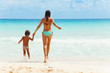 Child and woman holding hands on sea background