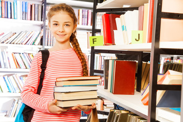Smiling girl holds books near shelf in library