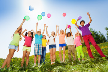 Children standing with arms up to flying balloons