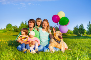 Smiling family sit on grass with balloons and dog