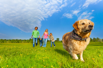 Running dog in front of happy family