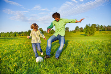Father and boy playing football together in park