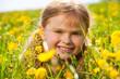 Beautiful smiling girl in dandelions portrait