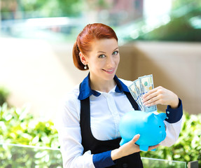 Businesswoman holding piggy bank depositing dollar bills