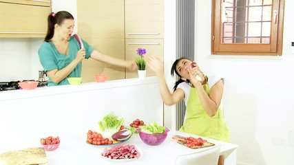 Two women singing with vegetables