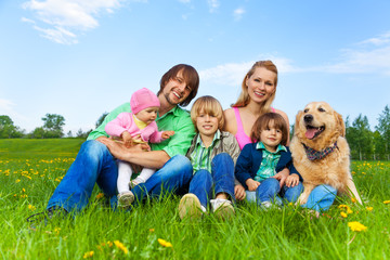 Smiling family sitting on green grass with dog
