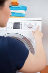 Housekeeper turning on washing machine