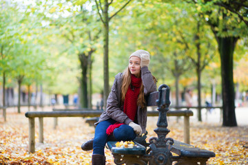 Girl sitting on a bench in park on a fall day