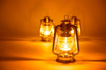 Burning three kerosene lamps background, concept light