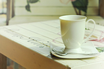 hot coffee on paint wooden table with vintage style