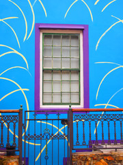 Blue wall of the house with purple window.  Porch with wicket