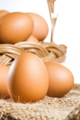 Close up fresh egg on brown burlap and basket on white backgroun