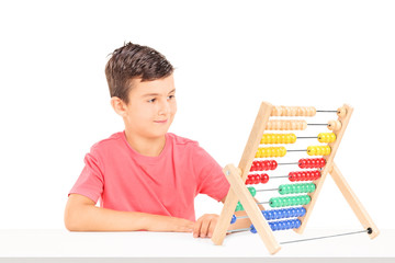 Little boy counting on abacus seated at a table