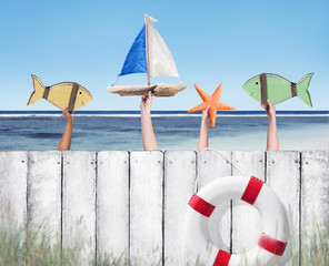Beach and Wooden Plank Fence with Hands Holding Toys