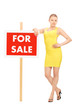 Woman standing by a for sale sign