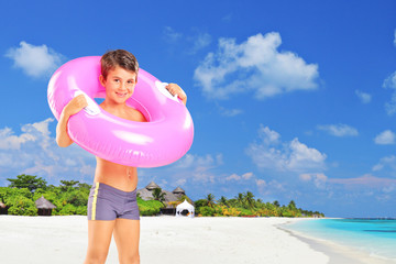 Boy standing on beach with swimming ring