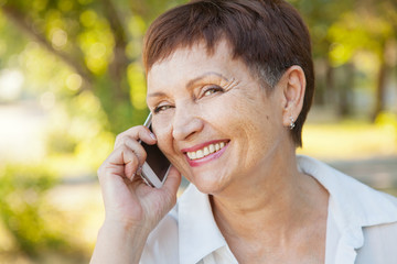 beautiful woman of 50 years with a mobile phone outdoors