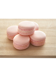 five pink macaroon on wooden tray