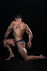 Muscular Men Flexing Muscles On Black Background