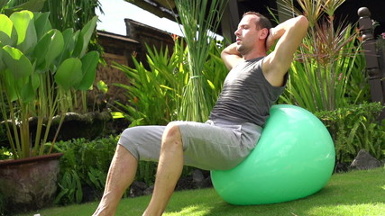 Man doing sit-ups on fitness ball in garden