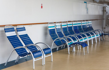 Blue and White Chairs on Deck of Ship