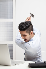 Furious businessman destroying his laptop with a hammer.
